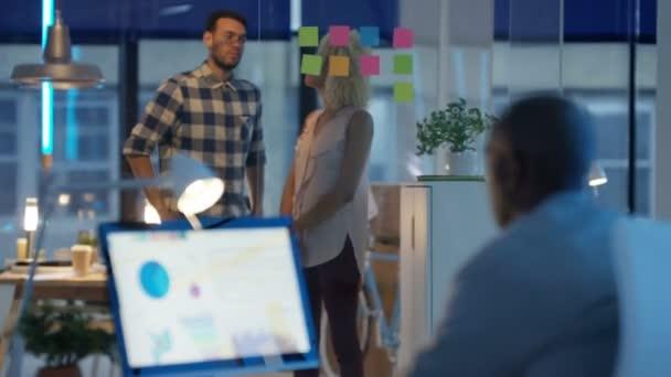 Příležitostné obchodní tým v moderní kanceláři pracuje na počítači a brainstorming s poznámkou