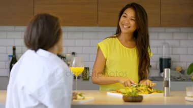 Cheerful female friends chatting in the kitchen while preparing a meal