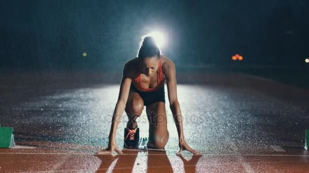 4 k Female athlete training presso la pista di atletica al buio e sotto la pioggia