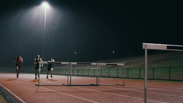 4K Competitive athletes running and jumping over hurdles at athletics track