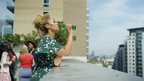 4K Portrait of smiling woman drinking beer and looking at view at rooftop party