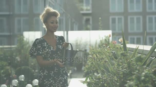 4K Portrait of smiling woman watering plants in city rooftop garden