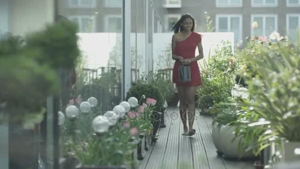 4K Attractive young woman watering plants in city rooftop garden