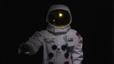4K Astronaut using interactive touch screen on black background