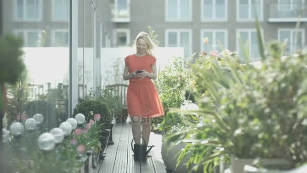 4K Attractive young woman watering her plants in city rooftop garden