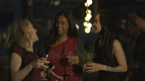 4K Happy mixed ethnicity group of friends drinking and dancing at rooftop party