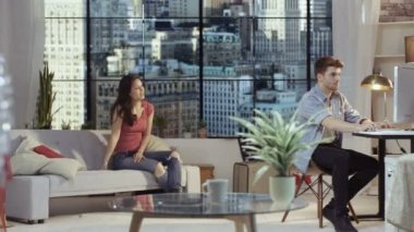 4K Couple relaxing in New York city apartment girl encouraging boyfriend to dance with her