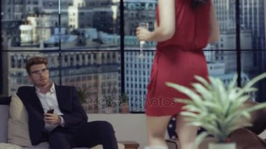 4K Fashionable young couple relaxing and drinking champagne in apartment with New York buildings on the background