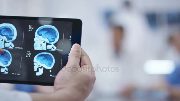 4K Medical team in a meeting. Hands holding tablet in foreground with brain scan