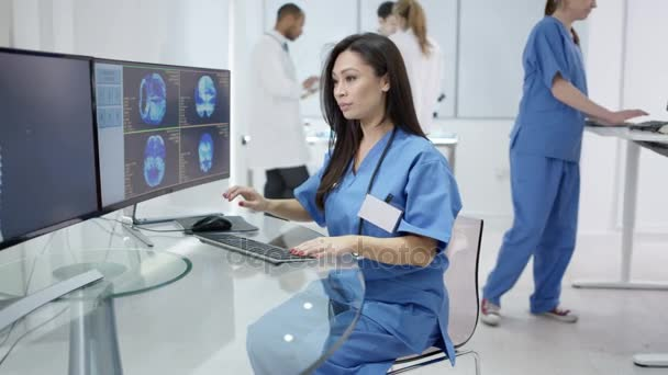 4K Portrait of smiling doctor in modern clinic looking at patient scans on computer