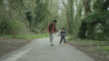 4K Happy father and son having fun outdoors, walking in the countryside