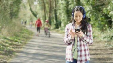 4K Happy attractive woman relaxing outdoors listening to music on smartphone