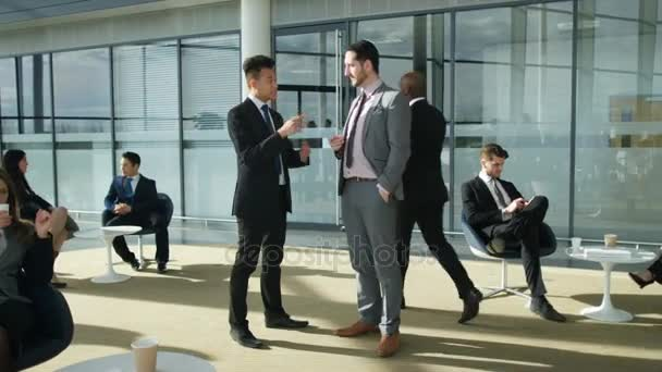 4K Businessmen having a conversation in crowded area of large modern office