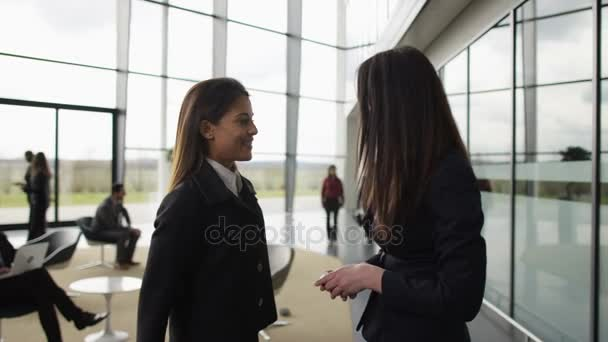 4K Businesswomen shaking hands in crowded area of large modern office