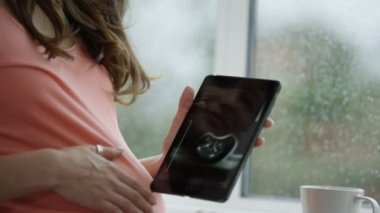 4K Pregnant woman at home, feeling her tummy and looking at baby scan on tablet