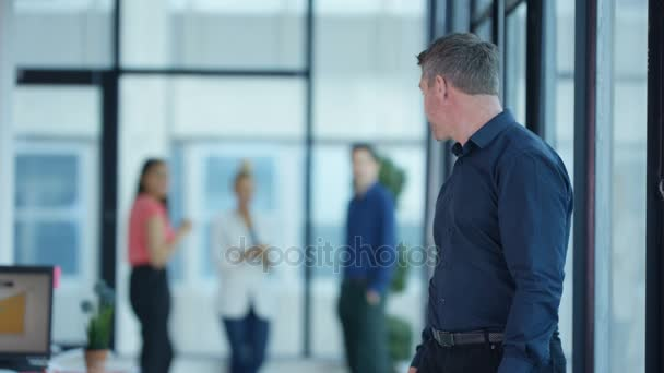 4K Portrait smiling casual businessman with coworkers standing in background