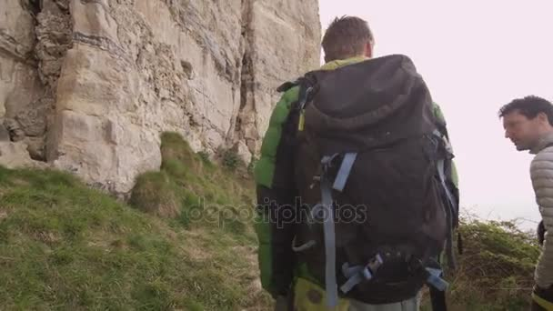 4K Male rock climbers hiking to location to begin a climb