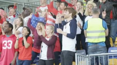 4K Excited fans with US flag in sports crowd, clapping and cheering on their team