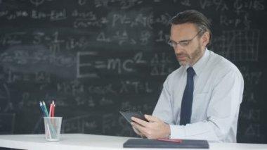 4K Man using computer tablet in classroom, studying math formulas on blackboard