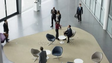 4K Diverse business group in meeting area of large modern office building