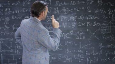 4K Portrait smiling academic man studying math formulas on blackboard