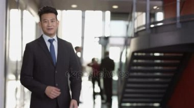 4K Portrait of smiling successful businessman in large modern office building