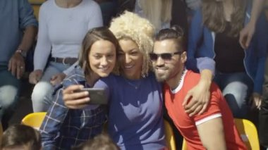 4K Friends sitting in the crowd at sports event possing for selfie with phone