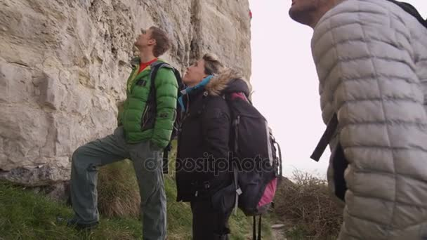 4K Group of rock climbers standing at base of cliff and planning their climb