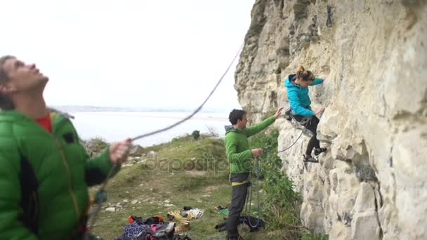 4K Group of rock climbers beginning their climb on rocky cliff