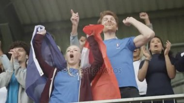 4K Excited fans with French flag in sports crowd, celebrating and cheering on team