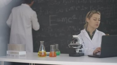 4K Scientist working in lab with colleague writing maths formulas on blackboard