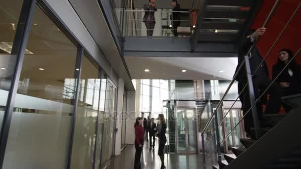 4 k velké rozmanité obchodní skupina pohybující se kolem velké moderní kancelářská budova