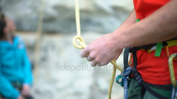 4K Rock climber attaching rope to his harness in preparation to climb