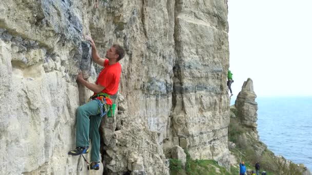 4K two people climbing natural vertical rock face - England, UK.