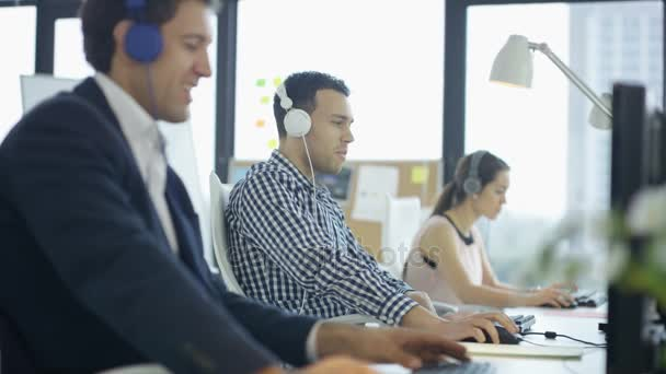 4K Happy workers in office working and listening to music through headphones