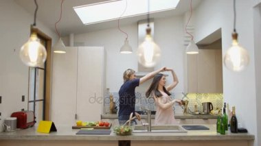 Happy affectionate couple dancing while they preparing a meal together in the kitchen at home.