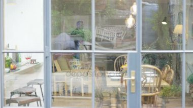 Couple with real estate agent, looking at home to buy or rent, view from outside looking in through window.