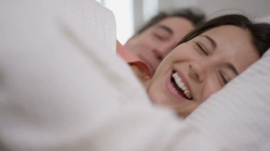 4K Happy couple enjoying early morning affections in the bedroom
