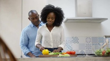 Affectionate couple preparing a meal together in the kitchen at home.