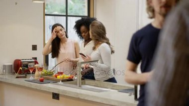 Happy mixed ethnicity group of friends socializing at home. Preparing a meal, chatting and looking at smartphone.