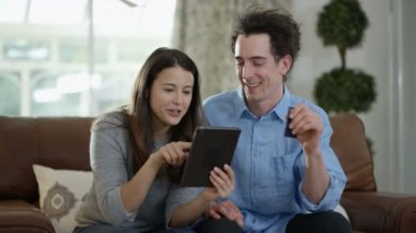 4K Cheerful couple with tablet and credit card shopping online at home