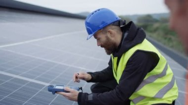 4K Technicians checking the panels at solar energy installation