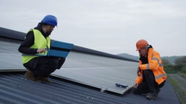 4K Technicians with laptop checking the panels at solar energy installation