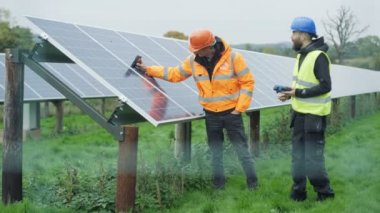 4K Technicians working at solar energy plant, checking the panels and talking