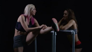 4K Fit young women working out together and stretching out leg muscles