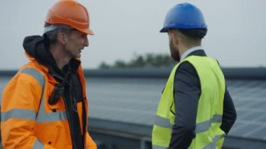 4K Businessman and engineer discussing operations at solar energy plant