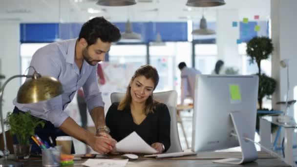 Designer arbeiten an ihrem Schreibtisch in Kreativbüro und im Gespräch mit Kollegen