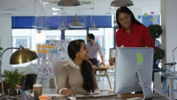 Designer arbeiten an ihrem Schreibtisch in Kreativbüro und im Gespräch mit Kollegin