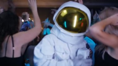 4K Happy party crowd and funny astronaut dancing in the club