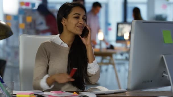 Young businesswoman talking on cell phone at her desk with colleagues working in background.